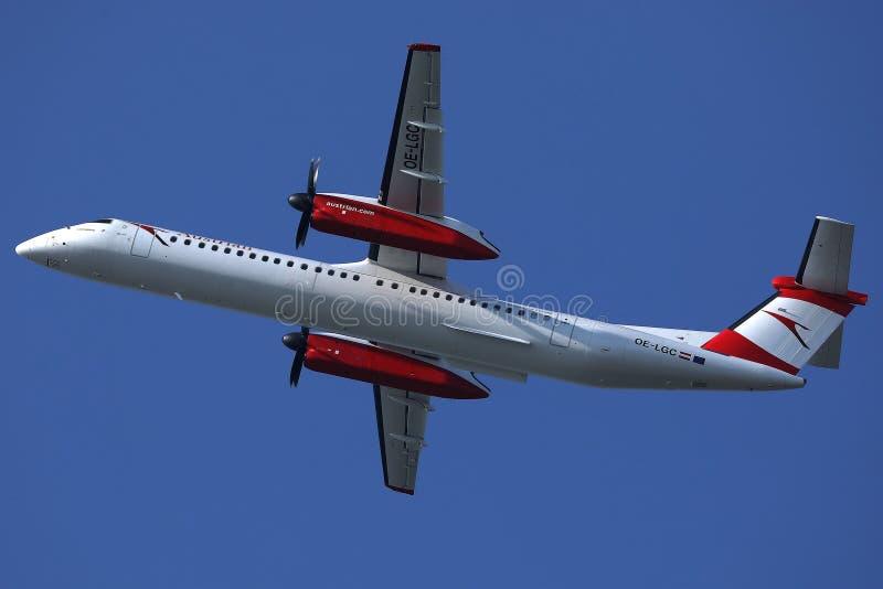 Μικρό αεριωθούμενο αεροπλάνο της Austrian Airlines που πετά επάνω στον ουρανό στοκ εικόνα