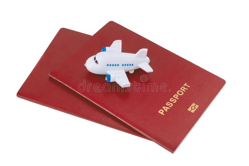 Μικρό αεροπλάνο παιχνιδιών πάνω από δύο κόκκινα διαβατήρια στοκ φωτογραφία