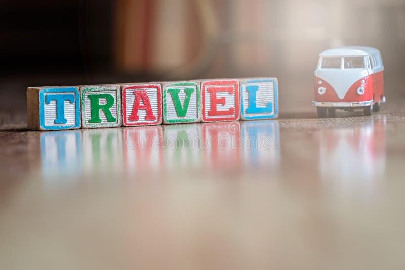 Μικρό αυτοκίνητο παιχνιδιών και ξύλινοι φραγμοί που συλλαβίζουν το ταξίδι λέξης στοκ φωτογραφία με δικαίωμα ελεύθερης χρήσης