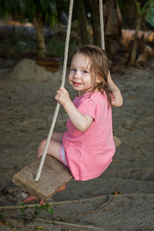 Μικρό ευτυχές κορίτσι μικρών παιδιών που φορά το ρόδινο φόρεμα στην ταλάντευση στοκ φωτογραφίες με δικαίωμα ελεύθερης χρήσης