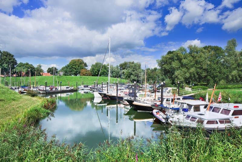Μικρό λιμάνι με τα γιοτ που βρίσκονται σε ένα πράσινο περιβάλλον, Woudrichem, οι Κάτω Χώρες στοκ εικόνες