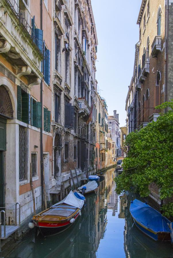 Μικρό κανάλι μέσο της Βενετίας τις παραδοσιακές ξύλινες βάρκες που σταθμεύουν με μπροστά από την είσοδο σπιτιών στοκ εικόνες με δικαίωμα ελεύθερης χρήσης