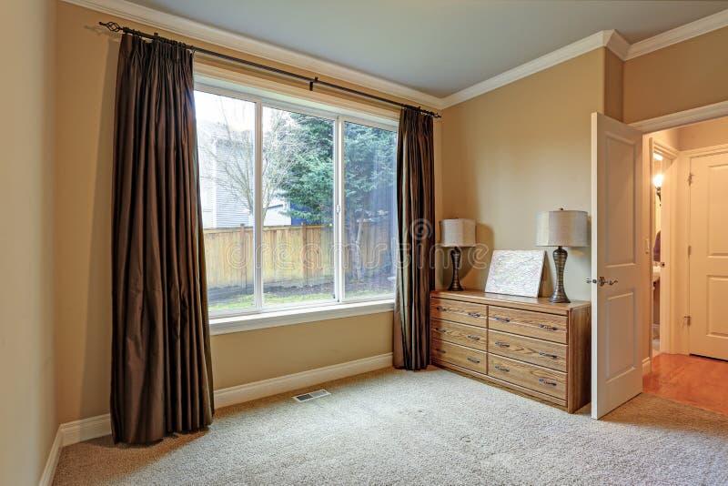 Μικρό κενό δωμάτιο με τις καφετιές κουρτίνες μεταξιού στοκ φωτογραφίες