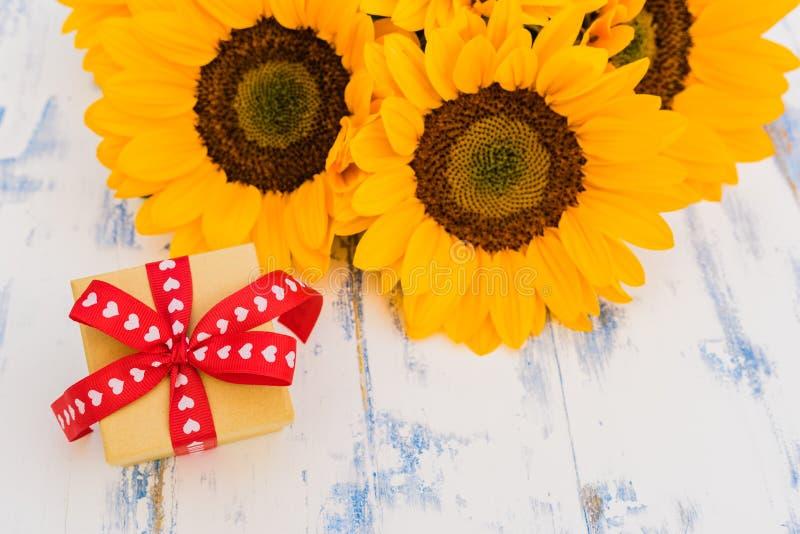 Μικρό κιβώτιο δώρων με την κορδέλλα καρδιών και την όμορφη δέσμη των λουλουδιών για την ημέρα μητέρων, την ημέρα βαλεντίνων ή τη  στοκ φωτογραφία με δικαίωμα ελεύθερης χρήσης