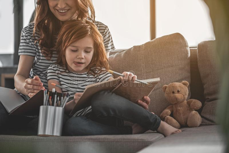Μικρό κοκκινομάλλες σχέδιο κοριτσιών με προσήλωση με το mom της κοντινό στοκ εικόνες με δικαίωμα ελεύθερης χρήσης
