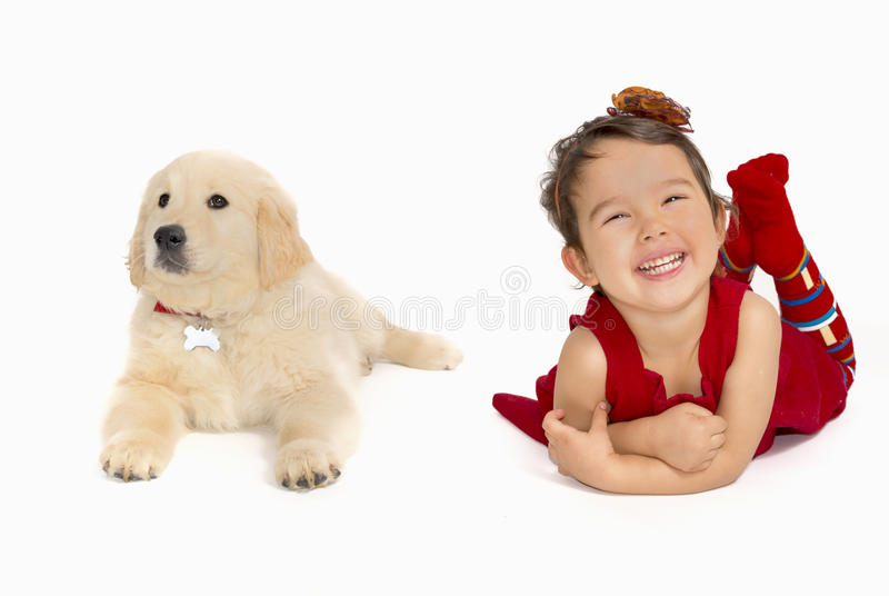 Μικρό κορίτσι ένα χρυσό retriever κουτάβι που απομονώνεται με στοκ φωτογραφία με δικαίωμα ελεύθερης χρήσης