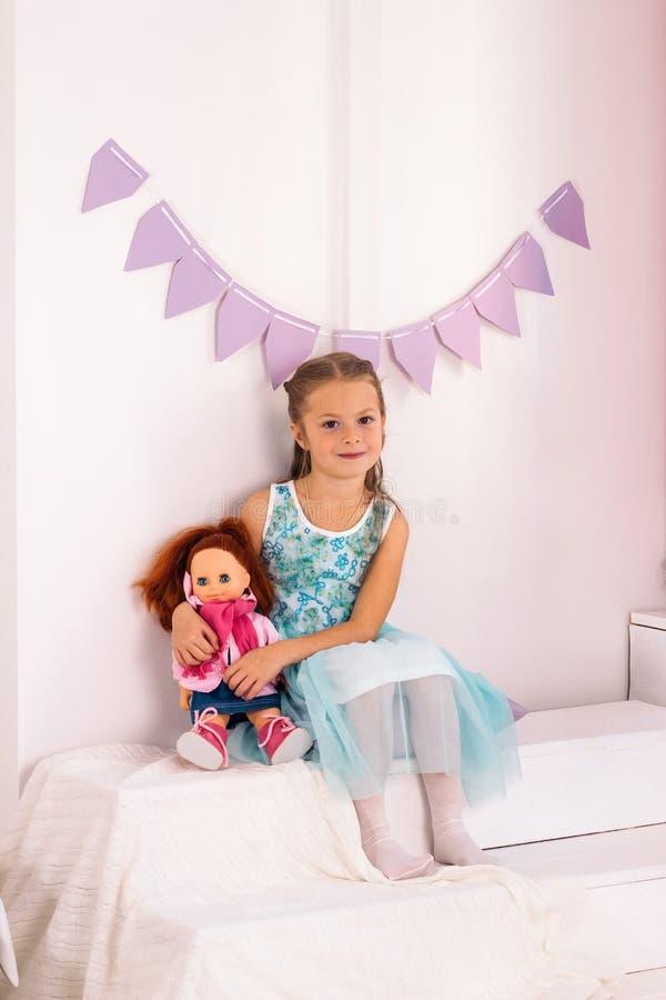 μικρό κορίτσι αγκαλιάζει μια κούκλα στο λευκό δωμάτιο στοκ εικόνες