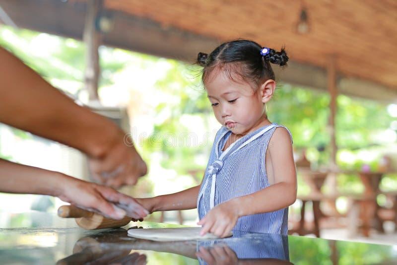 Μικρό κορίτσι διδασκαλίας μητέρων για τη χρησιμοποίηση της ξύλινης κυλώντας καρφίτσας στη ζύμη για την πίτσα στοκ εικόνες με δικαίωμα ελεύθερης χρήσης