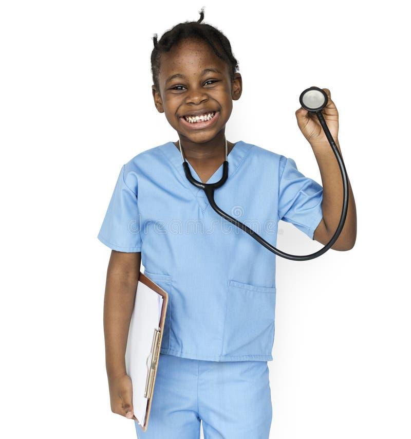 Μικρό κορίτσι ευτυχίας με το χαμόγελο εργασίας ονείρου γιατρών στοκ φωτογραφία