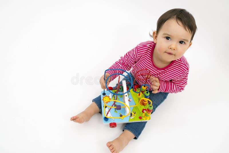 Μικρό κορίτσι ευχαριστημένο τα ζωηρόχρωμα ξύλινα παιχνίδια που απομονώνονται από στο λευκό στοκ φωτογραφία με δικαίωμα ελεύθερης χρήσης