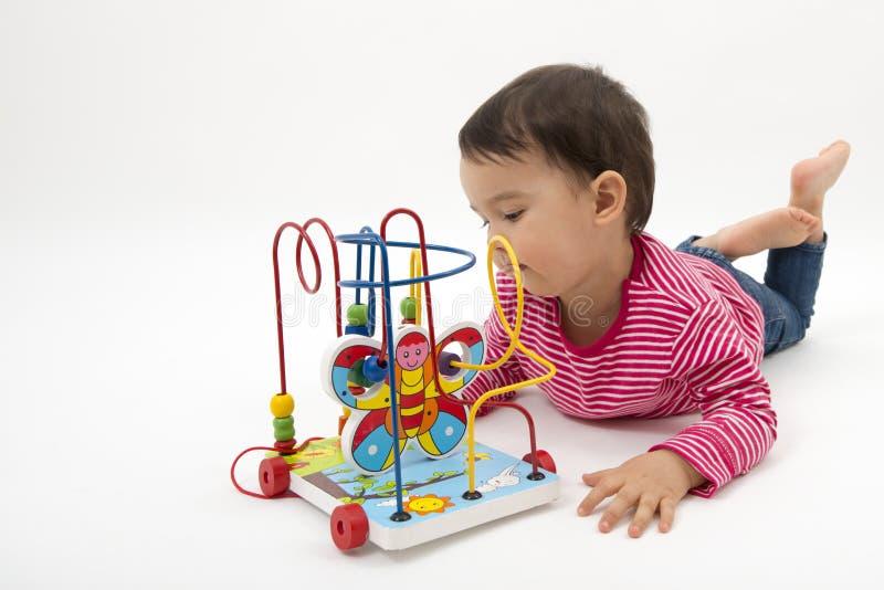 Μικρό κορίτσι ευχαριστημένο το ζωηρόχρωμο ξύλινο παιχνίδι που απομονώνεται από στο λευκό στοκ εικόνες