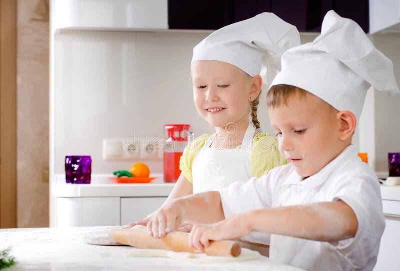 Μικρό κορίτσι και αγόρι που κατασκευάζουν τη σπιτική πίτσα στοκ εικόνες