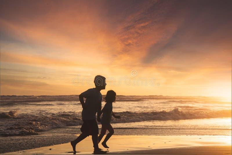 Μικρό κορίτσι και αγόρι που τρέχουν στην παραλία στοκ εικόνες