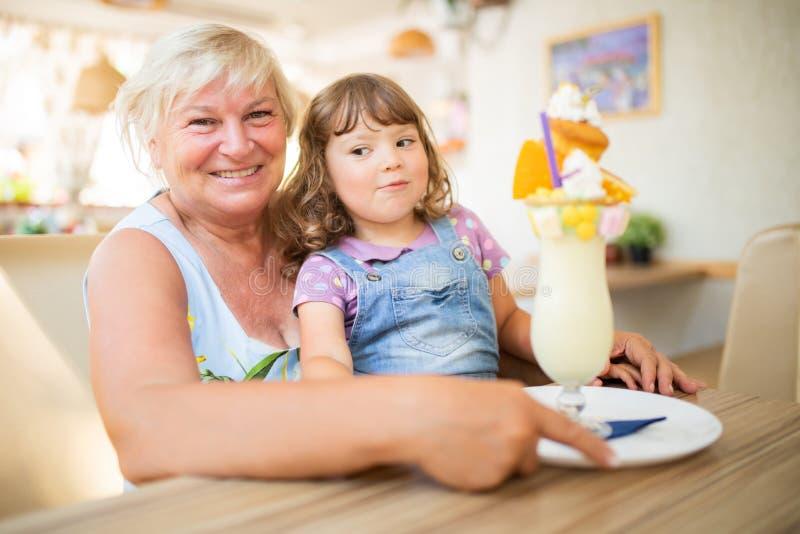 Μικρό κορίτσι και η γιαγιά της που τρώνε το παγωτό στο εστιατόριο στοκ εικόνες με δικαίωμα ελεύθερης χρήσης
