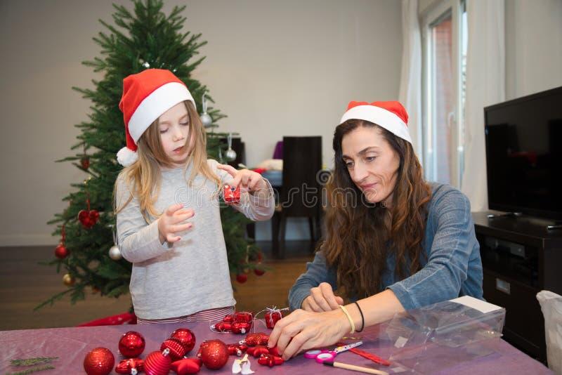 Μικρό κορίτσι και η μητέρα της που προετοιμάζουν τα στολισμούς για το Christma στοκ εικόνες