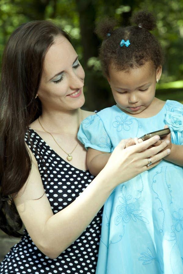 Μικρό κορίτσι και η μητέρα της στο τηλέφωνο στοκ φωτογραφία με δικαίωμα ελεύθερης χρήσης