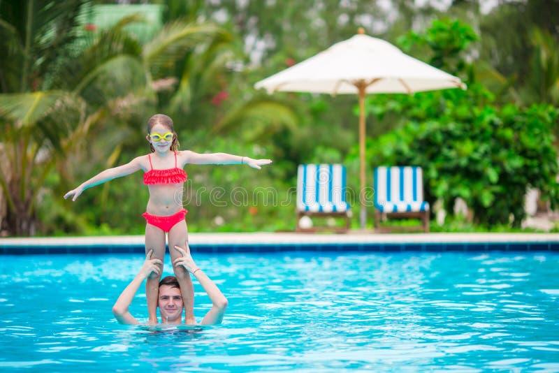 Μικρό κορίτσι και πατέρας που έχουν τη διασκέδαση υπαίθρια στην πισίνα στοκ εικόνες με δικαίωμα ελεύθερης χρήσης