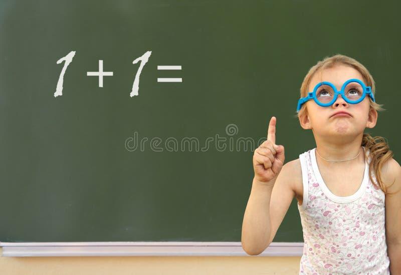 Μικρό κορίτσι και πράσινος πίνακας στοκ φωτογραφία