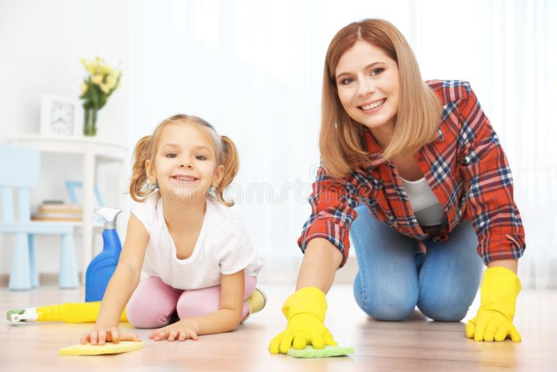 Μικρό κορίτσι και το καθαρίζοντας πάτωμα μητέρων της στοκ εικόνες