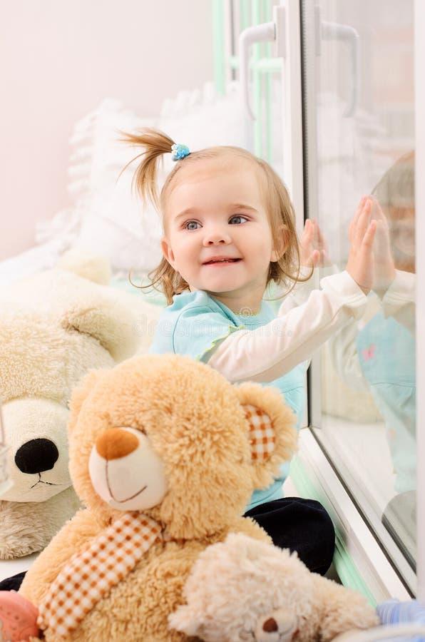 μικρό κορίτσι κοντά σε ένα παράθυρο στοκ εικόνα