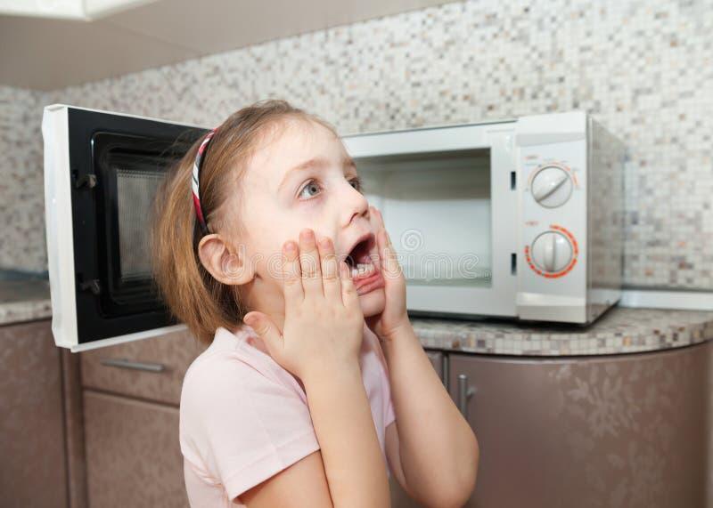 Μικρό κορίτσι κοντά στην επικίνδυνη συσκευή κουζινών στοκ εικόνες