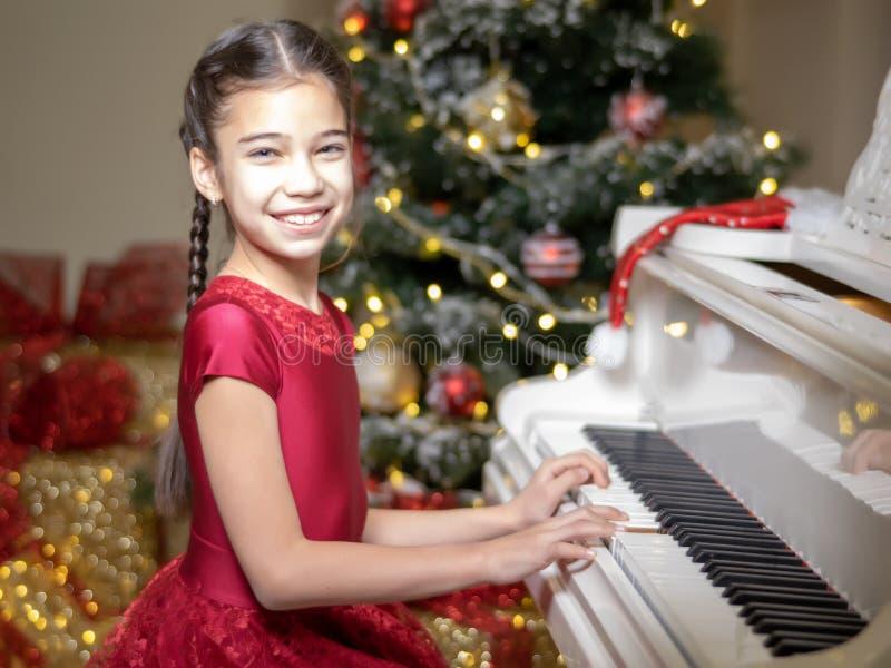 Μικρό κορίτσι κοντά στο πιάνο και το χριστουγεννιάτικο δέντρο στοκ εικόνες με δικαίωμα ελεύθερης χρήσης