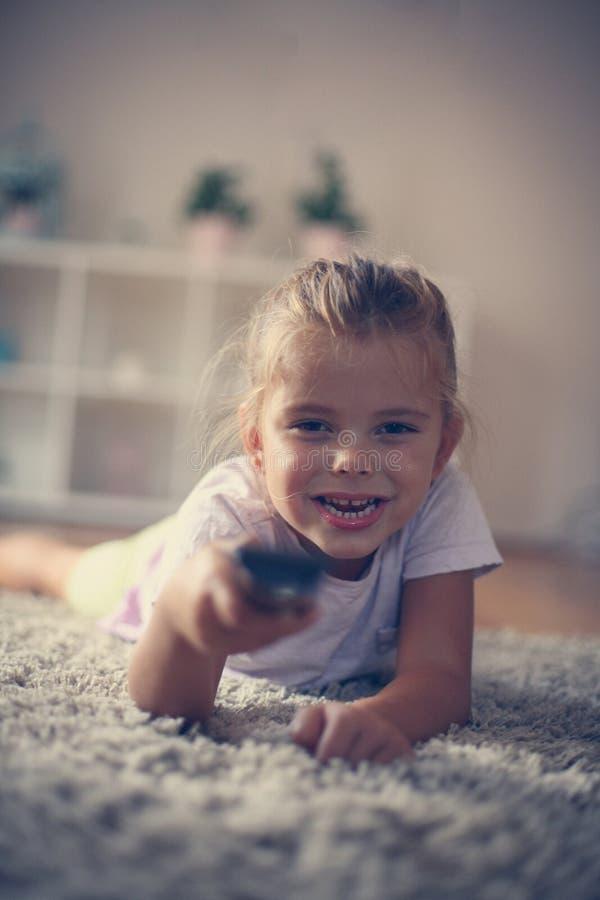 Μικρό κορίτσι λ που αλλάζει το τηλεοπτικό κανάλι με μακρινό στοκ φωτογραφία με δικαίωμα ελεύθερης χρήσης