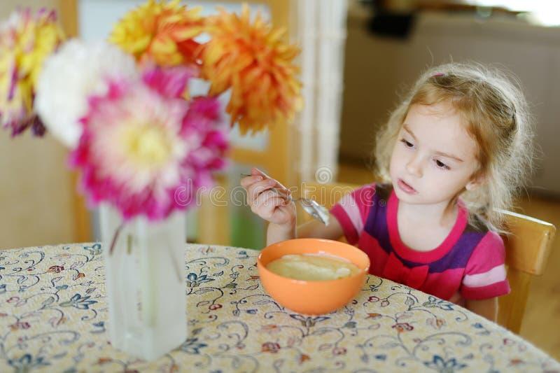 Μικρό κορίτσι με ένα κουτάλι του κουάκερ στοκ εικόνες