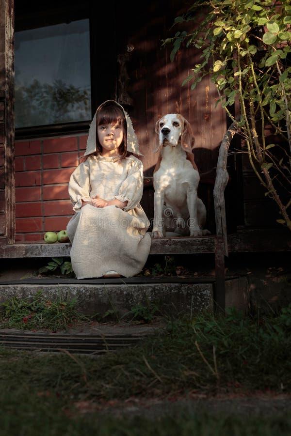 Μικρό κορίτσι με ένα σκυλί σε ένα θερινό βράδυ κοντά στο παλαιό σπίτι στοκ εικόνες