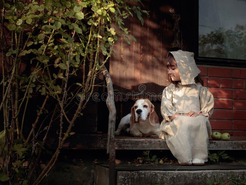Μικρό κορίτσι με ένα σκυλί σε ένα θερινό βράδυ κοντά στο παλαιό σπίτι στοκ φωτογραφίες