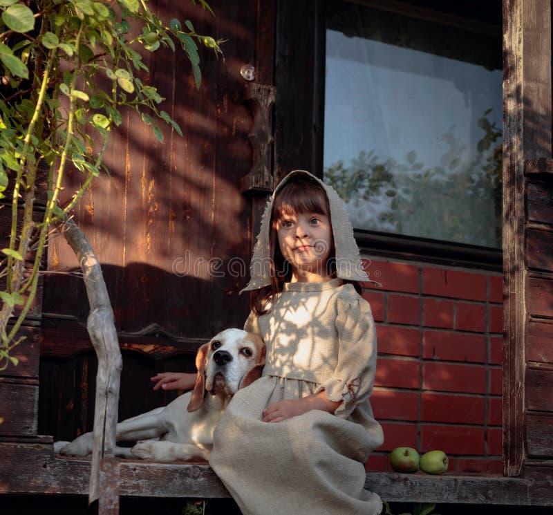 Μικρό κορίτσι με ένα σκυλί σε ένα θερινό βράδυ κοντά στο παλαιό σπίτι στοκ φωτογραφίες με δικαίωμα ελεύθερης χρήσης