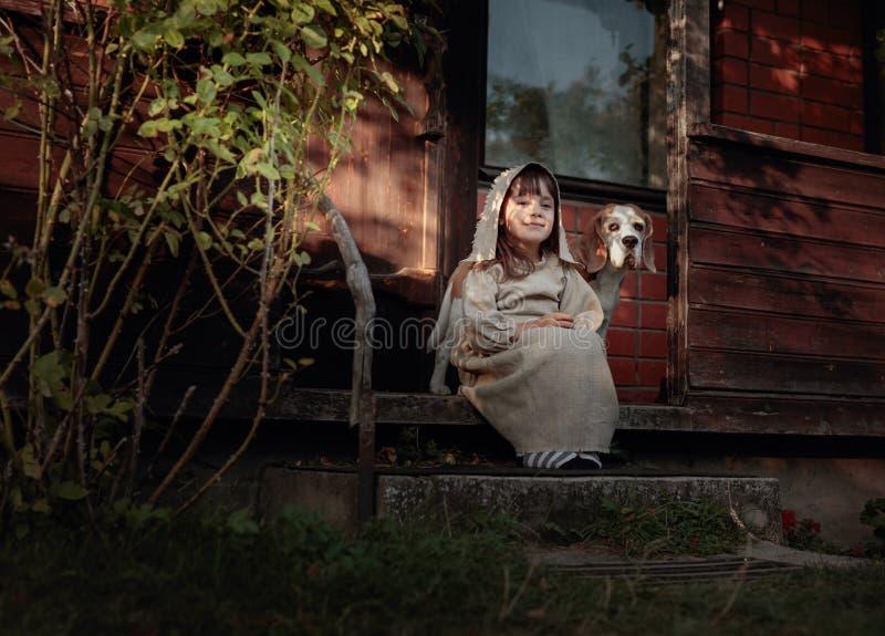 Μικρό κορίτσι με ένα σκυλί σε ένα θερινό βράδυ κοντά στο παλαιό σπίτι στοκ εικόνες με δικαίωμα ελεύθερης χρήσης