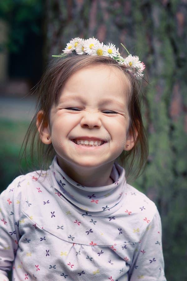 Μικρό κορίτσι με ένα στεφάνι των μαργαριτών στο κεφάλι της στοκ εικόνες με δικαίωμα ελεύθερης χρήσης