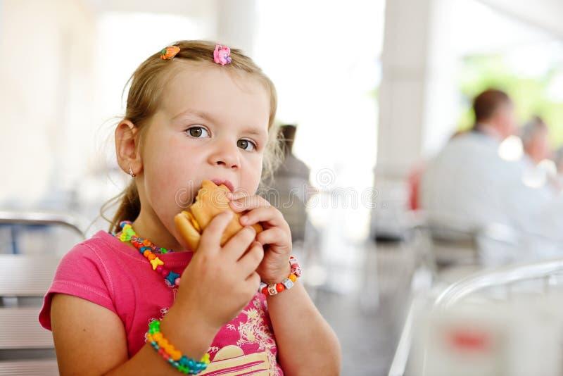 Μικρό κορίτσι με ένα χάμπουργκερ στοκ εικόνες