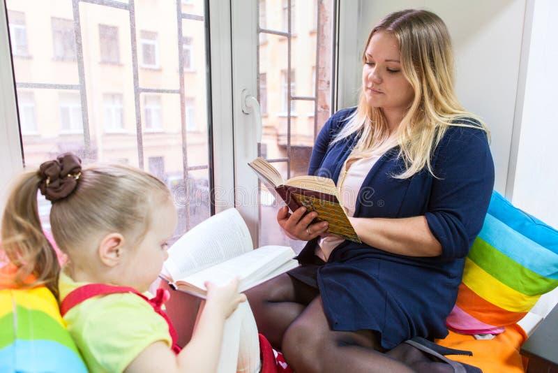 Μικρό κορίτσι με διαβασμένα τα μητέρα βιβλία στο windowsill στοκ εικόνες