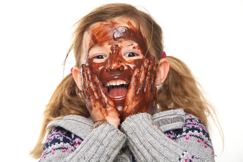 Μικρό κορίτσι με καλυμμένο το σοκολάτα πρόσωπο στοκ φωτογραφίες