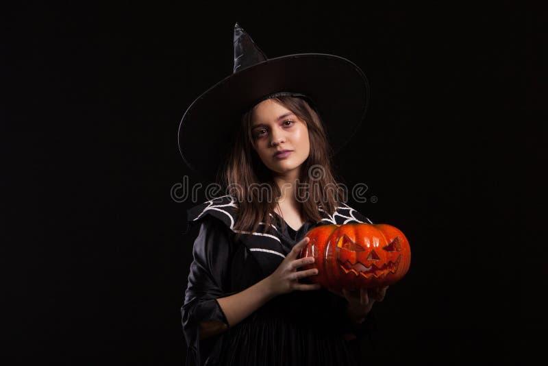 Μικρό κορίτσι με μια σοβαρή έκφραση που κάνει μια περίοδο κρατώντας για αποκριές στοκ εικόνες