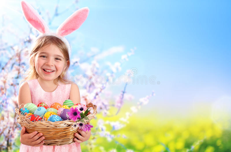 Μικρό κορίτσι με τα αυγά και το λαγουδάκι αυτί-Πάσχα καλαθιών στοκ εικόνες