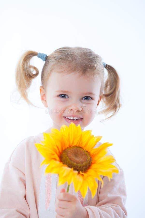 Μικρό κορίτσι με τα λουλούδια και ένα δώρο στοκ φωτογραφίες με δικαίωμα ελεύθερης χρήσης