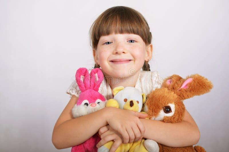 Μικρό κορίτσι με τα μαλακά παιχνίδια στοκ φωτογραφίες