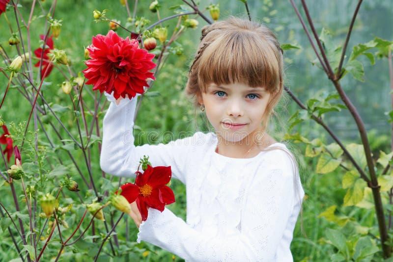 Μικρό κορίτσι με τα λουλούδια στον κήπο στοκ εικόνα