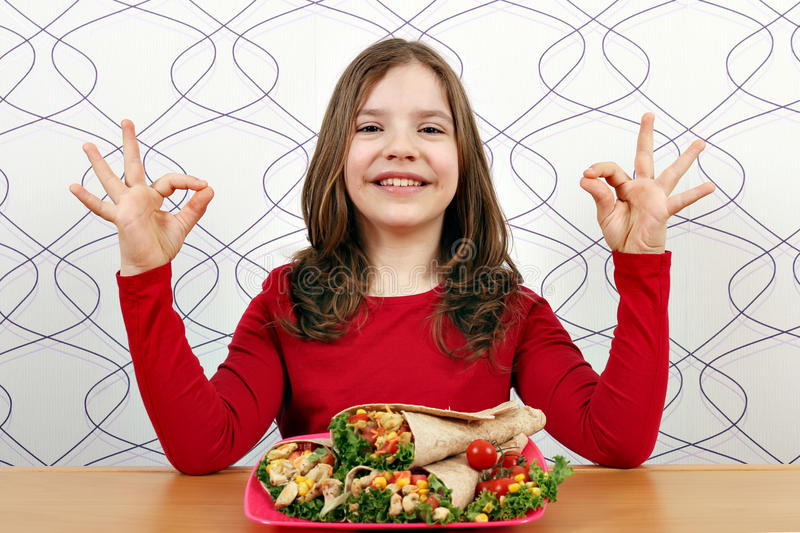 Μικρό κορίτσι με τα burritos και το εντάξει σημάδι χεριών στοκ φωτογραφίες