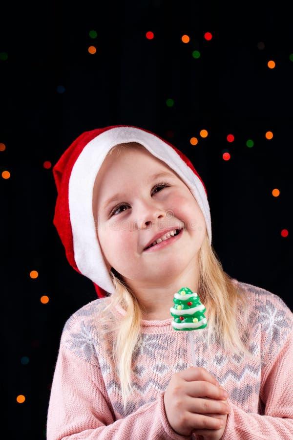 Μικρό κορίτσι με την καραμέλα Χριστουγέννων στοκ εικόνες