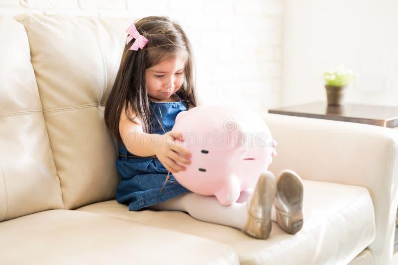 Μικρό κορίτσι με την κενή piggy τράπεζα στοκ φωτογραφίες