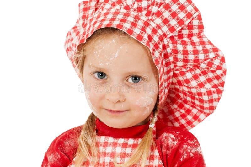 Μικρό κορίτσι με την κινηματογράφηση σε πρώτο πλάνο καπέλων αρχιμαγείρων στοκ εικόνες