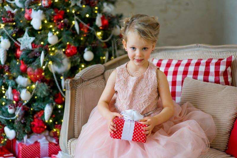 Μικρό κορίτσι με τη συνεδρίαση δώρων Χριστουγέννων κοντά στο δέντρο στοκ φωτογραφία