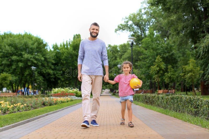 Μικρό κορίτσι με τη σφαίρα και ο πατέρας της που περπατά υπαίθρια στοκ φωτογραφία με δικαίωμα ελεύθερης χρήσης