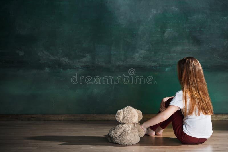 Μικρό κορίτσι με τη teddy συνεδρίαση αρκούδων στο πάτωμα στο κενό δωμάτιο Έννοια αυτισμού στοκ φωτογραφία