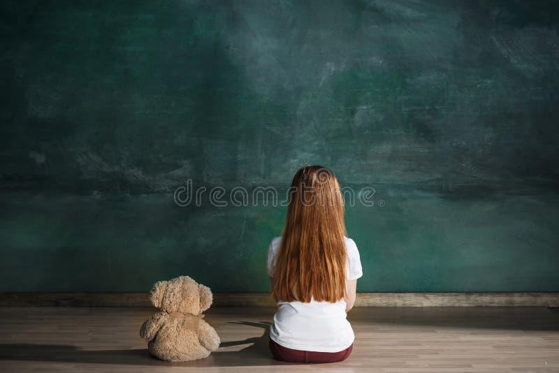Μικρό κορίτσι με τη teddy συνεδρίαση αρκούδων στο πάτωμα στο κενό δωμάτιο Έννοια αυτισμού στοκ φωτογραφίες