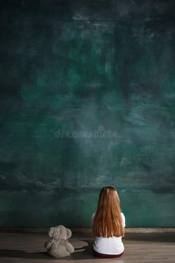 Μικρό κορίτσι με τη teddy συνεδρίαση αρκούδων στο πάτωμα στο κενό δωμάτιο Έννοια αυτισμού στοκ εικόνες